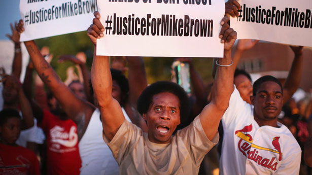 Protestor+in+Ferguson+promoting+the+hashtag+%22%23justiceformikebrown%22+who+was+a+victim+of+police+violence.