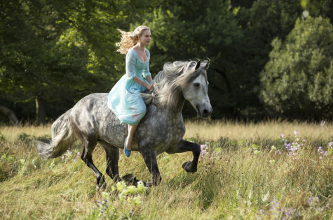 Lily James as Cinderella, depicted galloping on a beautiful horse through fields of lavender
