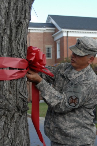 United States Soldier tying the famous ribbon symbol around a tree in support of Red Ribbon Week