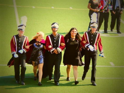The band leadership wears smiles on their faces, marching back to greet the band in the stands.