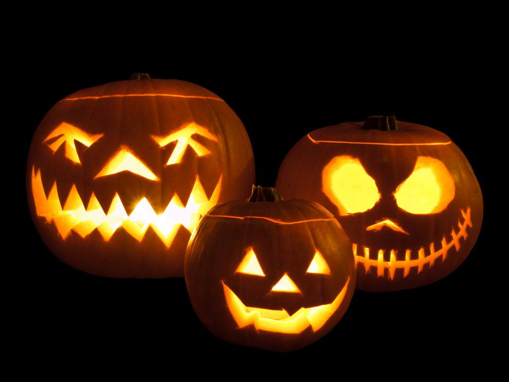 Carved from pumpkins, these jack-o'-lanterns are lit with small candles.