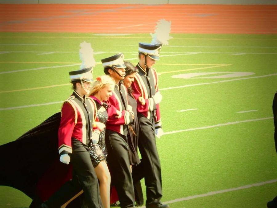 The+Drum+Majors%2C+Drum+Captain%2C+and+Color+Guard+Captains+exit+the+field%2C+linking+arms.