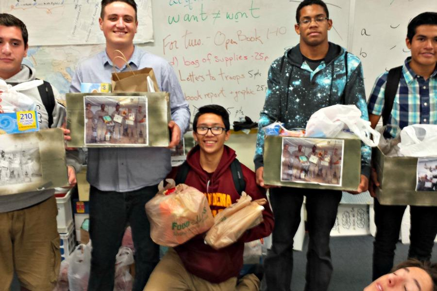 Students hold boxes of items being sent to our troops over seas.